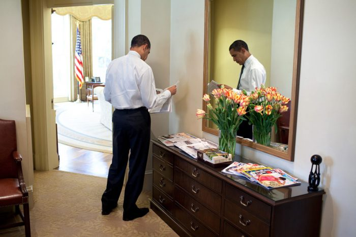 President Barack Obama standing and reading a paper in the White House